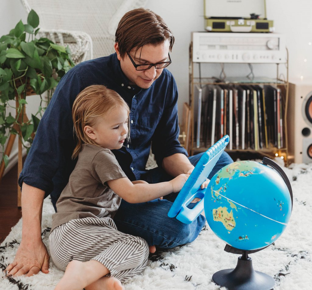 parent and kid homeschooling with globe