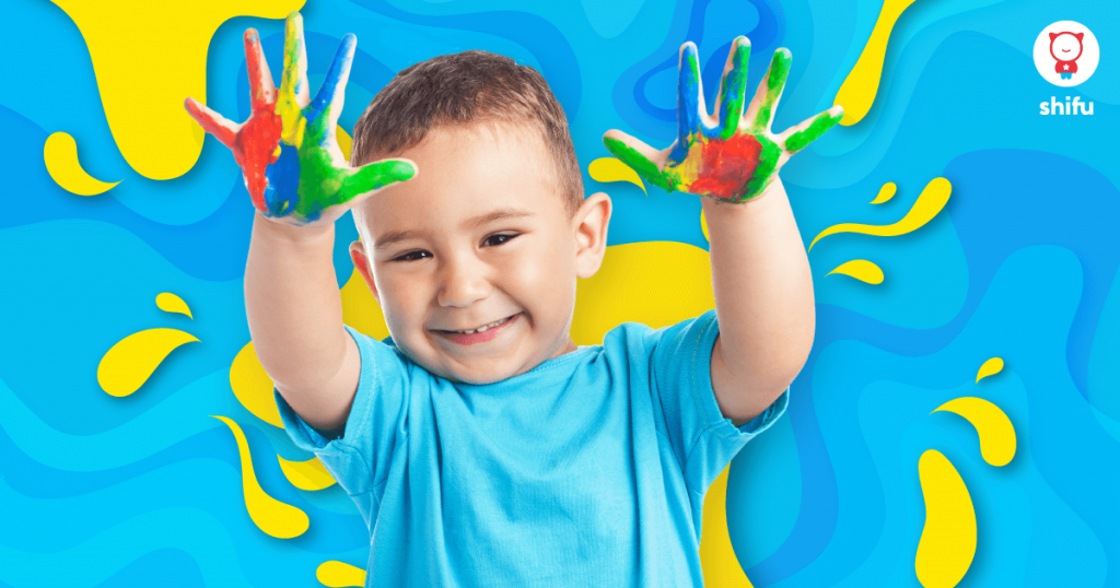 kid-with-painted-hands-smiling-at-camera