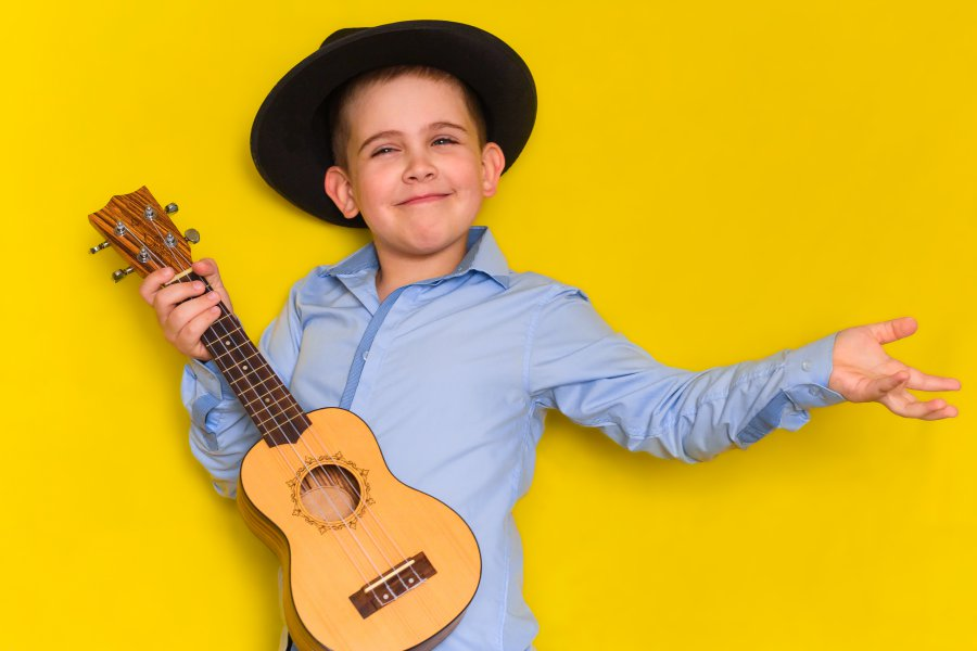 beautiful cute little boy in hat and shirt keeps guitar isolated on yellow background