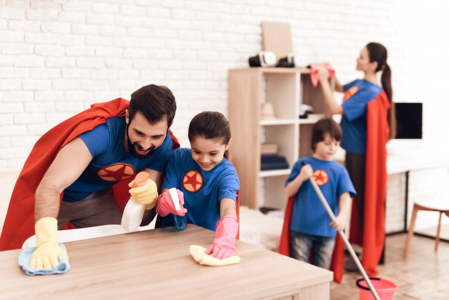 The family in suits of superheroes is cleaned at home.