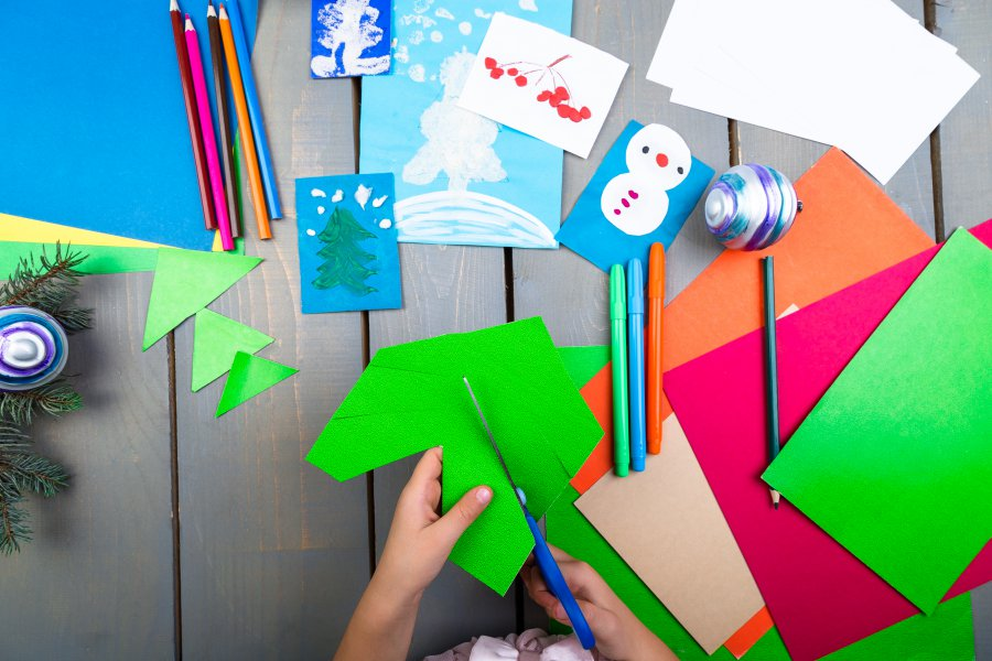 Child hands make handmade christmas toys from cardboard. Children's DIY concept