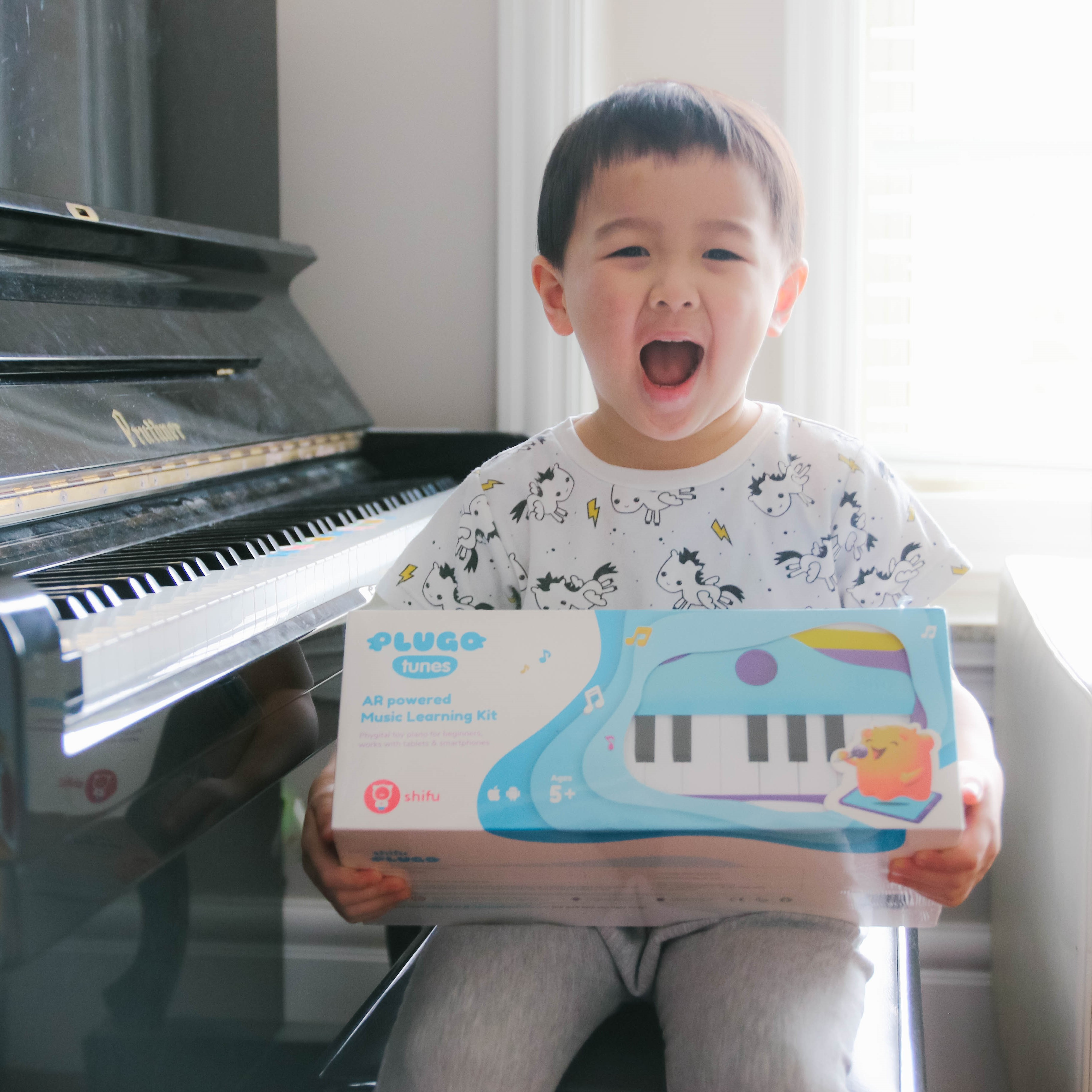 kid sitting besides a piano with Plugo tunes box