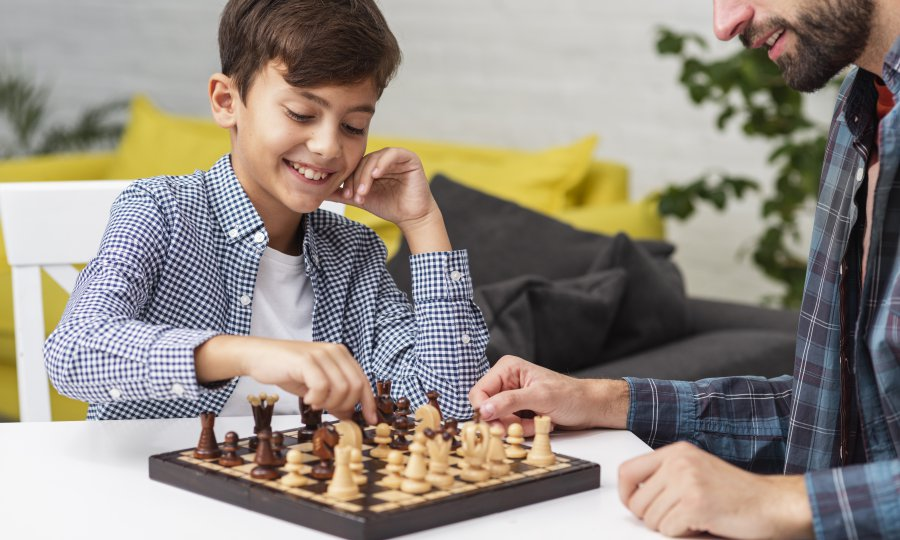boy smiling and playing chess