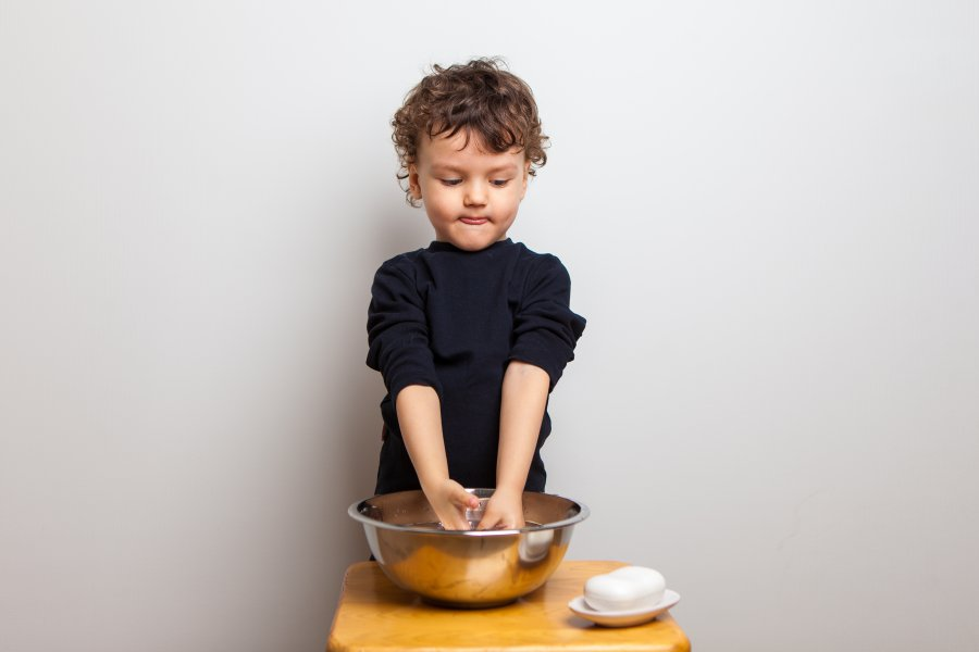 cute curly boy, a child in a black T-shirt washes his hands with soap in a bowl with water in the studio on a white background. prevention of acute respiratory viral infections and coronavirus