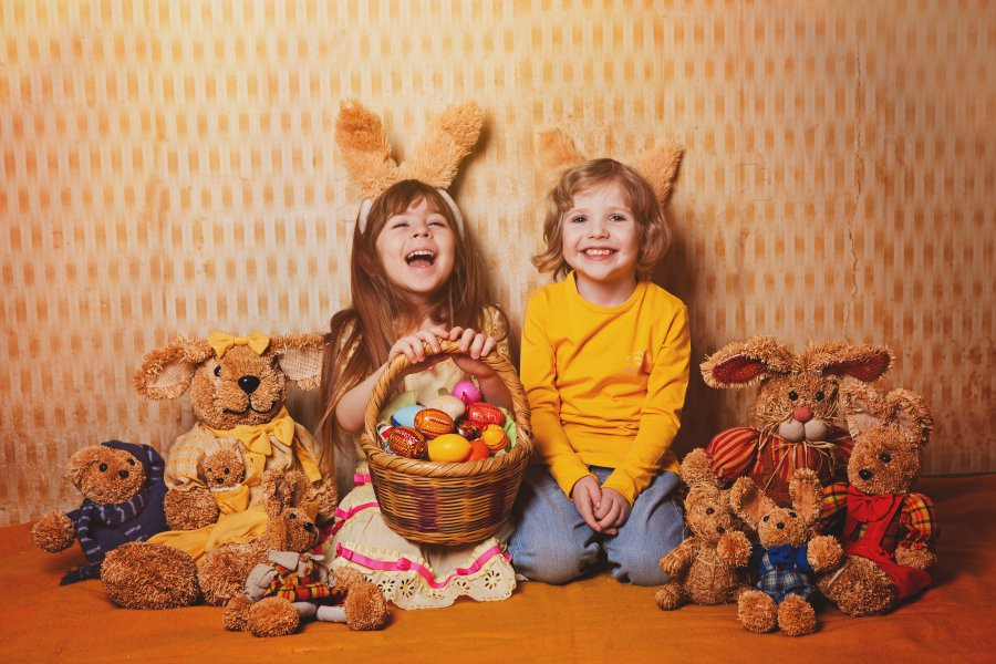 boy and girl with rabbit ears sitting around a lot of straw and plush hares, vintage style